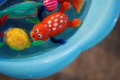 La pequeña muñeca está en el agua en el tanque Foto de archivo