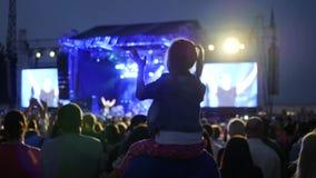 La pequeña muchacha agradable aplaudió en el concierto, muchas luces en etapa, brazos de la palmada de los fans, cámara lenta, mu almacen de metraje de vídeo