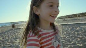 La pequeña muchacha alegre corre lejos, para, y da vuelta alrededor en una orilla de mar, en la puesta del sol en el slo-MES almacen de metraje de vídeo