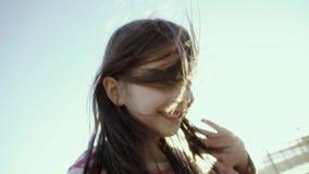La pequeña muchacha alegre se coloca, grita, y corre en una playa del mar, en la puesta del sol en el slo-MES almacen de video