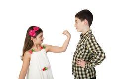 La pequeña muchacha amenaza al muchacho del puño fotos de archivo libres de regalías