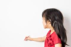 La pequeña muchacha asiática está escribiendo en una pared blanca Fotos de archivo libres de regalías