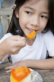 La pequeña muchacha asiática goza de la empanada anaranjada del queso. Imagen de archivo