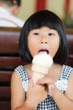 La pequeña muchacha asiática goza de su helado Imagen de archivo libre de regalías