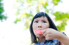 La pequeña muchacha asiática goza de su helado Fotos de archivo