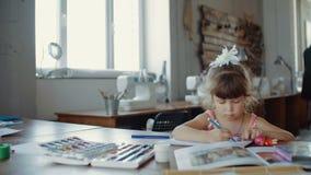 La pequeña muchacha bonita adentro dibuja con los marcadores coloreados en la tabla en sitio metrajes
