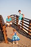La pequeña muchacha bonita hermosa está caminando en el puente de madera a su padre Imágenes de archivo libres de regalías