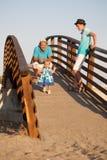 La pequeña muchacha bonita hermosa está caminando en el puente de madera a su padre Imagen de archivo libre de regalías
