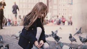 La pequeña muchacha caucásica sienta pájaros de alimentación afuera Cámara lenta El niño femenino feliz alimenta palomas en la ca metrajes