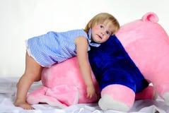 La pequeña muchacha con el elefante rosado grande Foto de archivo