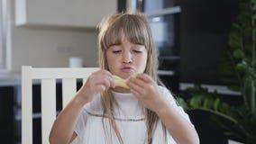 La pequeña muchacha con el pelo largo en el vestido blanco hace los bigotes de la pasta cruda al prepararse las galletas para cue almacen de video