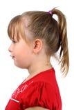 La pequeña muchacha con la cola de potro se vistió en el rojo aislado Imagen de archivo libre de regalías