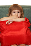 La pequeña muchacha con una almohada roja Fotos de archivo