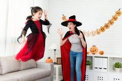 La pequeña muchacha de la bruja del horror salta del sofá foto de archivo