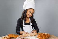 La pequeña muchacha de piel morena rueda la pasta El niño aprende cocinar Sombrero de la ropa y del cocinero Imagen de archivo