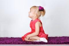 La pequeña muchacha de risa se está sentando en una alfombra púrpura en el estudio Imagen de archivo