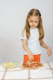 La pequeña muchacha de seis años que se coloca en la tabla y asperja con la pizza de queso rallado Imagen de archivo