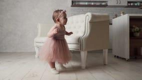 La pequeña muchacha del bebé en falda y vestido del tutú cerca del sofá aprende caminar almacen de metraje de vídeo