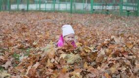 La pequeña muchacha divertida salta en una pila de hojas de otoño almacen de video