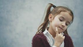 La pequeña muchacha dulce está en un fondo gris Al mismo tiempo el pensamiento, aumentando su mano para arriba recordaba la histo metrajes