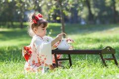 La pequeña muchacha en kimono se está sentando en la hierba Foto de archivo libre de regalías