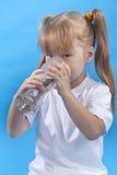 La pequeña muchacha es agua potable Imagen de archivo libre de regalías