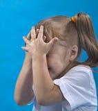 La pequeña muchacha es cubierta su cara Fotos de archivo