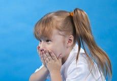 La pequeña muchacha está cubriendo su cara Foto de archivo libre de regalías