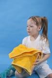 La pequeña muchacha está manteniendo la toalla amarilla aislada Fotos de archivo libres de regalías
