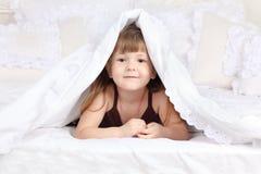 La pequeña muchacha feliz mira hacia fuera de debajo la manta Imagenes de archivo
