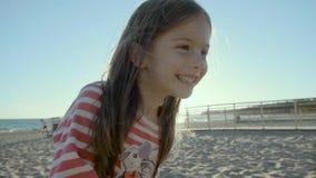 La pequeña muchacha feliz se coloca, corre, y se cae en una playa del mar, en la puesta del sol en el slo-MES metrajes