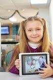 La pequeña muchacha feliz sostiene la tableta con la foto de su familia Imagen de archivo