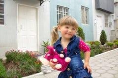 La pequeña muchacha hermosa camina con un juguete suave en sus manos en el aire abierto imagen de archivo libre de regalías