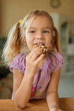 La pequeña muchacha hermosa come las galletas sabrosas Fotografía de archivo