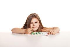 La pequeña muchacha hermosa con el cepillo pinta las flores fotografía de archivo libre de regalías