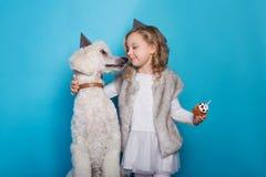 La pequeña muchacha hermosa con el perro celebra cumpleaños Amistad Amor Torta con la vela Retrato del estudio sobre fondo azul Foto de archivo libre de regalías