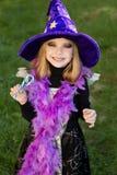 La pequeña muchacha hermosa con el traje de la bruja de Halloween que sonreía y ha coloreado el caramelo Fotografía de archivo