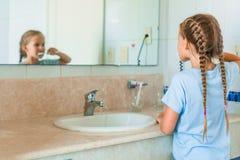 La pequeña muchacha hermosa con los dientes blancos cepilla los dientes en el cuarto de baño Imágenes de archivo libres de regalías