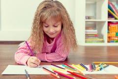 La pequeña muchacha hermosa dibuja el lápiz en el piso Fotografía de archivo libre de regalías