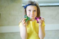 La pequeña muchacha hermosa en camiseta amarilla está jugando con dos hilanderos en manos Foto de archivo libre de regalías