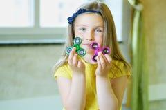La pequeña muchacha hermosa en camiseta amarilla está jugando con dos hilanderos en manos Imagen de archivo
