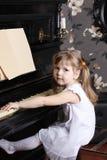 La pequeña muchacha hermosa en el vestido blanco se sienta en el piano Imagen de archivo