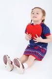 La pequeña muchacha hermosa en vestido se sienta en piso y lleva a cabo el corazón rojo imágenes de archivo libres de regalías