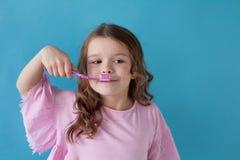 La pequeña muchacha hermosa limpia la odontología del cepillo de dientes de los dientes foto de archivo