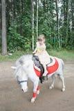 La pequeña muchacha hermosa monta el potro blanco imagen de archivo
