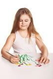 La pequeña muchacha hermosa pinta las flores sobre blanco foto de archivo libre de regalías