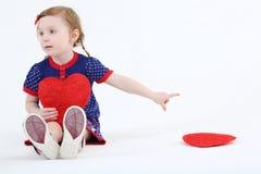 La pequeña muchacha hermosa se sienta con el corazón rojo fotos de archivo libres de regalías