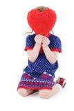 La pequeña muchacha hermosa se sienta y oculta la cara detrás del corazón rojo Fotos de archivo