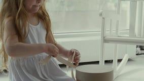 La pequeña muchacha linda ata un regalo con una cinta almacen de video