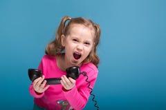La pequeña muchacha linda atractiva en camisa rosada con el mono y los pantalones azules habla un teléfono Foto de archivo libre de regalías
